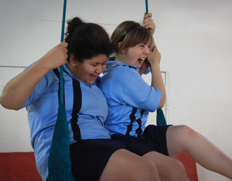 Two girls sitting on a swing, while laughing.