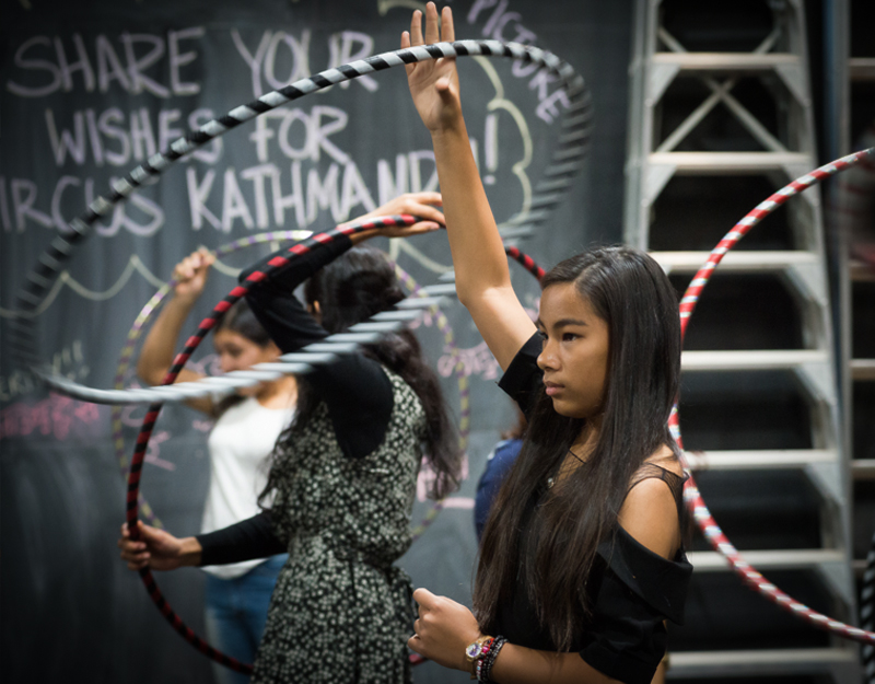 A young girl playing with a hoop in a workshop.