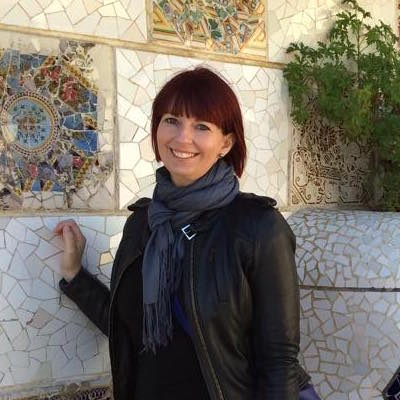 A woman smiling, while standing in front of a mosaic.