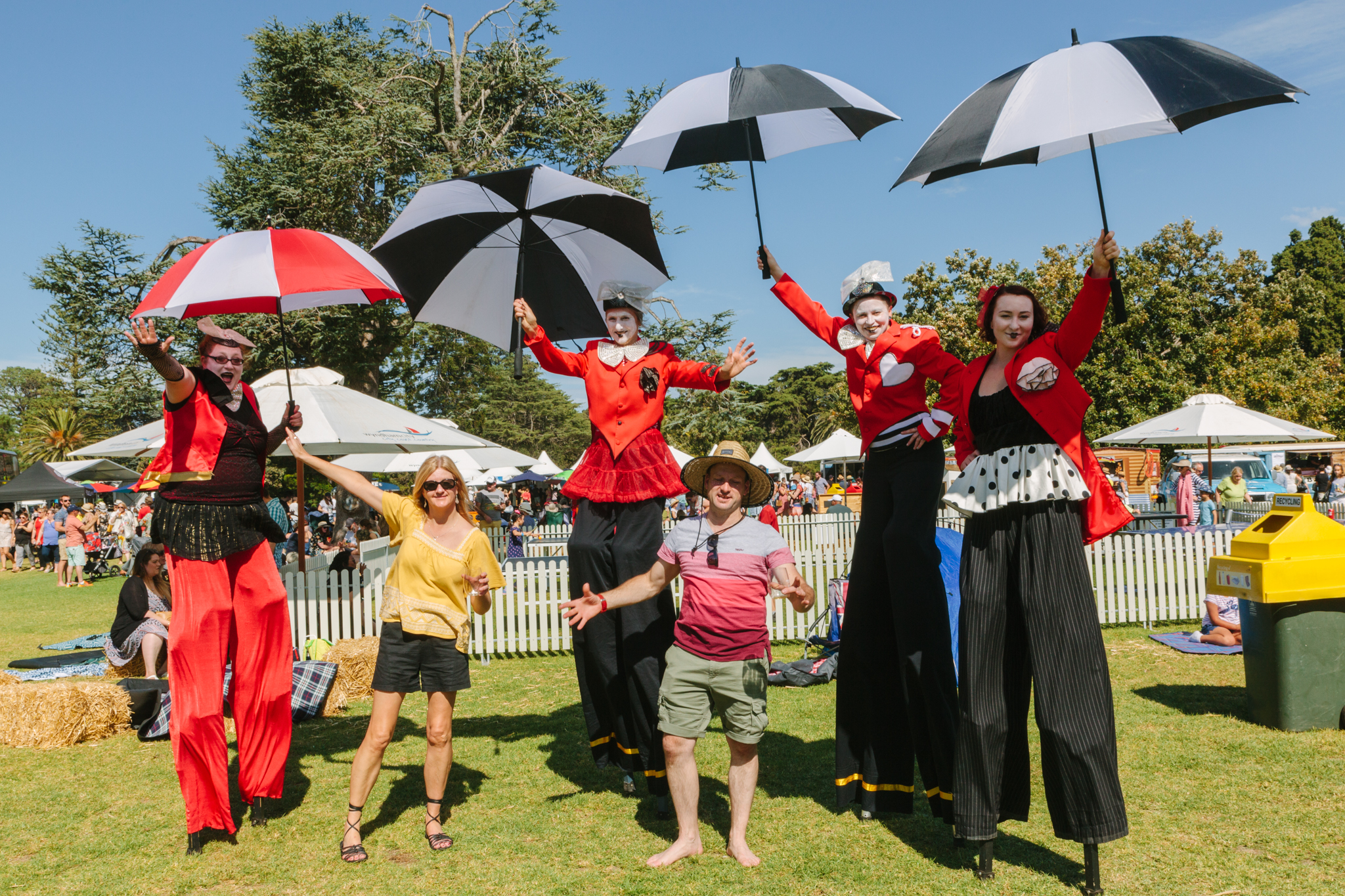 Two people posing with a group of performers on stilts while holding umbrellas.