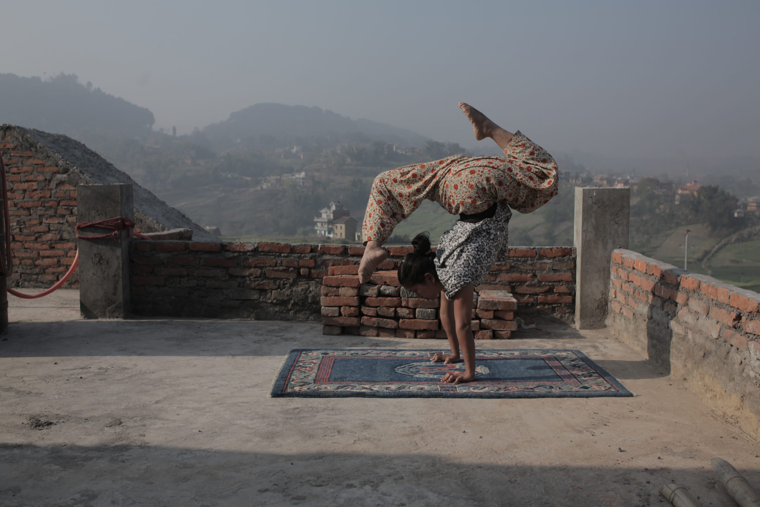 A woman doing a handstand atop a rooftop.