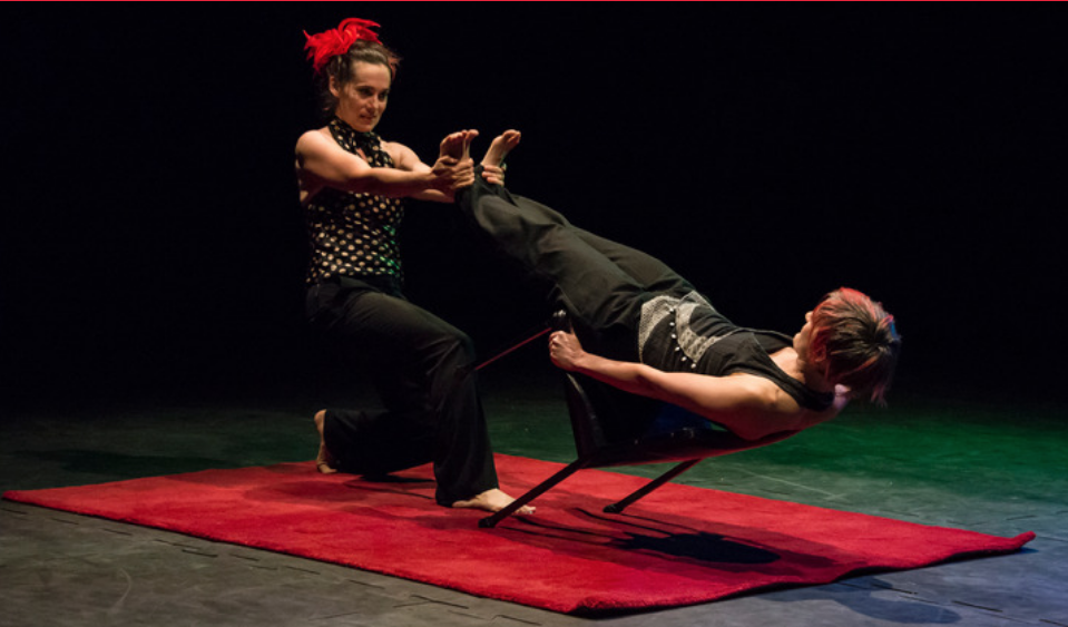 Two people performing on stage, one is kneeling and the other is balancing on a tilted chair.