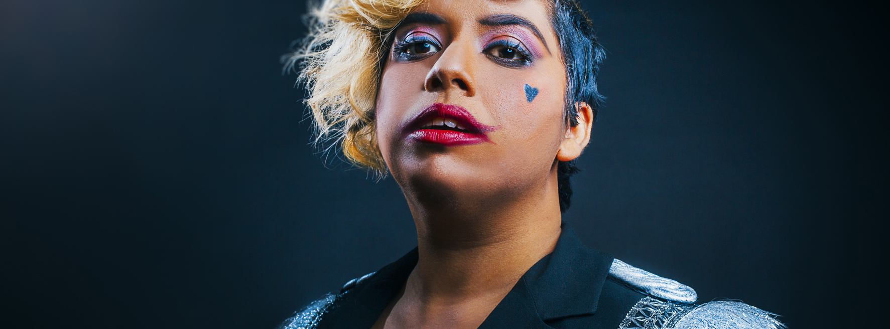 A woman with bold circus makeup on her face.