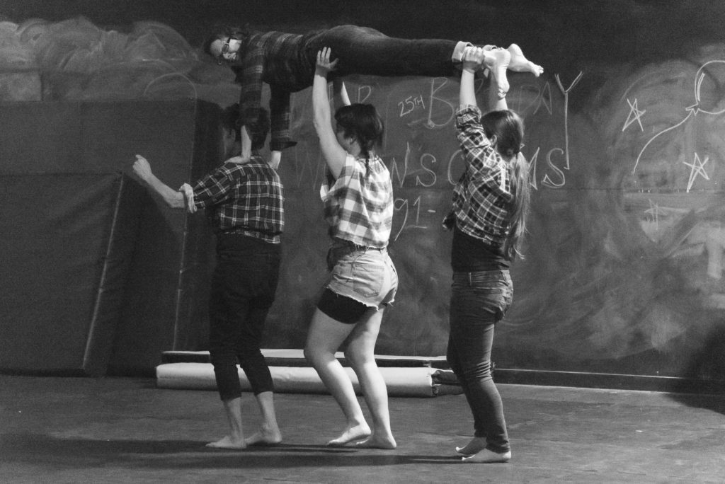 Three people holding one person above them.