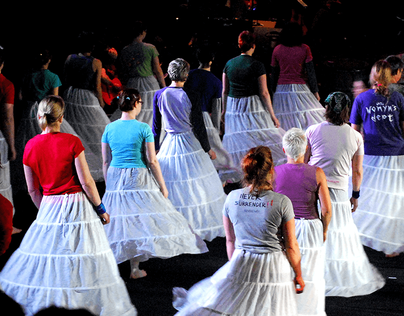 A group of people wearing white, hooped skirts.