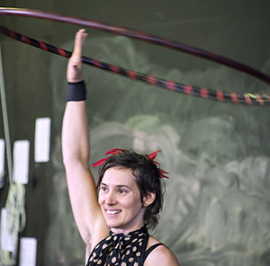 A woman playing with a hula hoop.