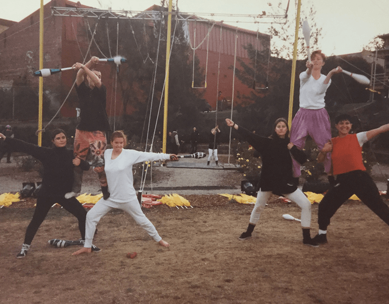 A group of people performing circus tricks outdoors.