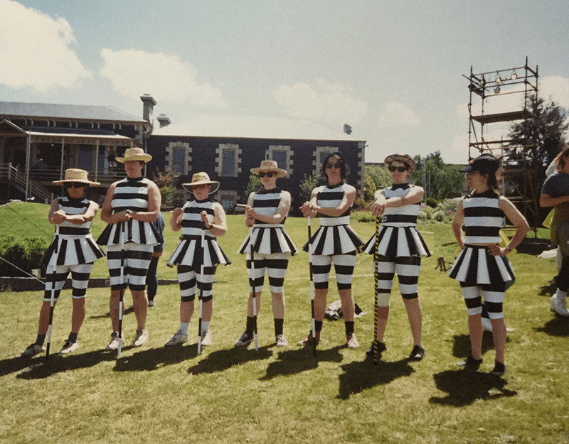 A group of people, dressed in a black and white striped outfits while holding canes.