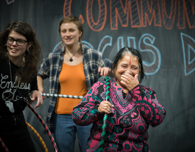 Three laughing women playing with hula hoops.