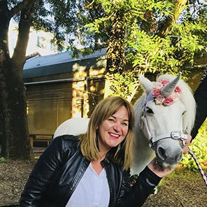 A smiling woman posing with a horse wearing a unicorn horn.