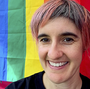 A woman smiling while standing in front of a rainbow background.