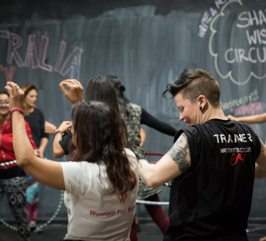 Women's Circus trainer teaching hula hoop to a group